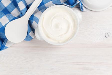 yaourts: La cr�me fra�che dans un bol sur la table en bois. Vue de dessus avec copie espace
