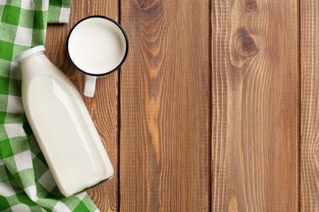 Melk beker en fles op houten tafel. Bovenaanzicht met een kopie ruimte