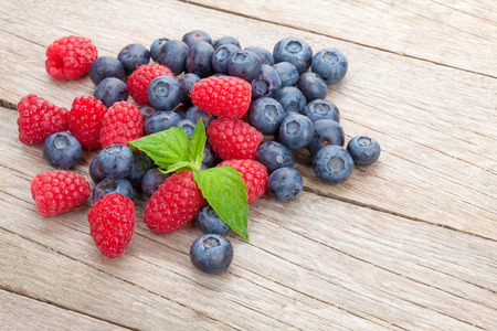 Blueberries and raspberries with mint leaf on wooden table photo