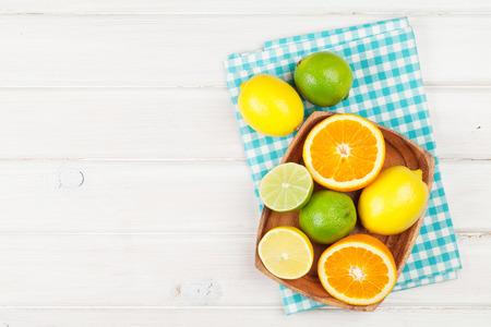 alimentacion sana: Las frutas cítricas. Las naranjas, limas y limones. Sobre fondo mesa de madera con espacio de copia Foto de archivo