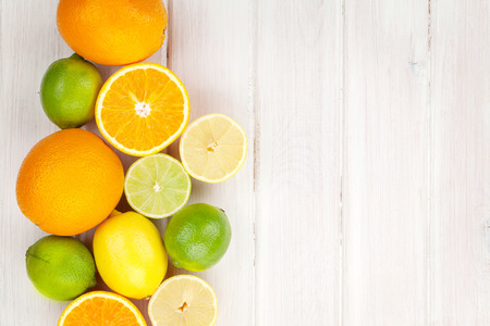 Citrus fruits. Oranges, limes and lemons. Over wooden table background with copy space photo
