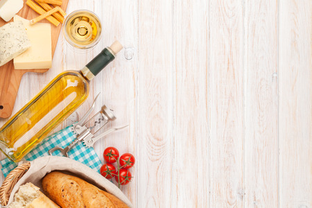 gourmet dinner: White wine, cheese and bread on white wooden table background. Top view with copy space Stock Photo