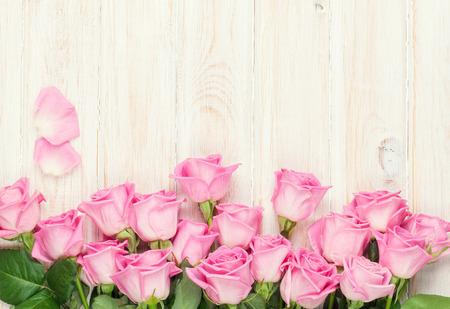 木製テーブルの上のピンクのバラの花束。コピー スペース平面図