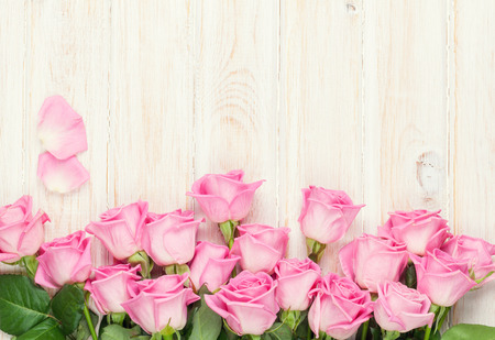 table: Pink roses bouquet over wooden table. Top view with copy space