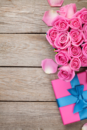 flower box: Valentines day background with gift box full of pink roses over wooden table. Top view with copy space
