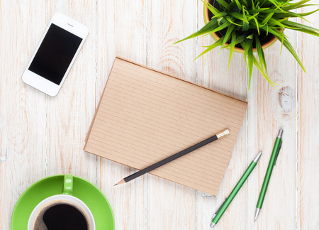 paper and pen: Office desk table with supplies, coffee cup and flower. Top view with copy space