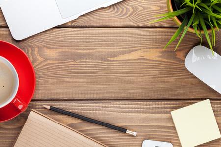 leveringen: Kantoor bureau tafel met computer, benodigdheden, koffiekop en bloem. Bovenaanzicht met een kopie ruimte