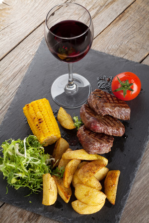 corn salad: Steak with grilled potato, corn, salad and red wine on wooden table Stock Photo