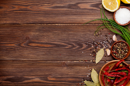 red kitchen: Various spices on wooden background. Top view with copy space