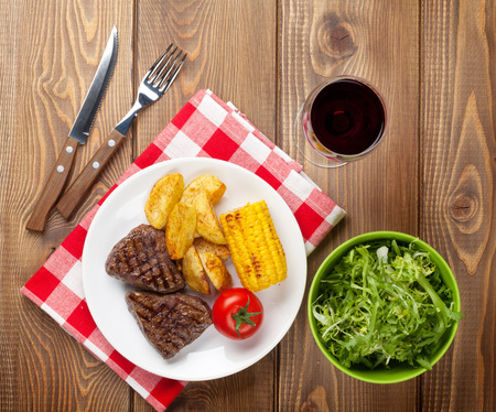 grilled potato: Steak with grilled potato, corn, salad and red wine on wooden table Stock Photo