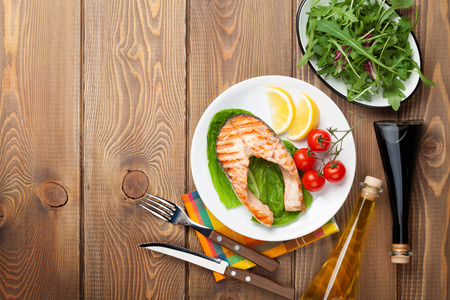 condiments: Grilled salmon, salad and condiments on wooden table. Top view with copy space