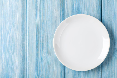 Empty plate on blue wooden background. Top view with copy space Standard-Bild