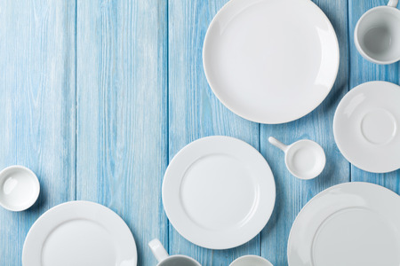 on white: Empty plates and bowls on blue wooden background. Top view with copy space Stock Photo