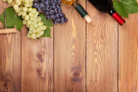Red and white wine bottles and bunch of grapes on wooden table with copy space