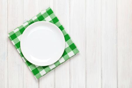 tabulka: Prázdný talíř a ručník přes dřevěný stůl pozadí. Pohled shora s kopií vesmíru Reklamní fotografie