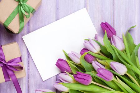 tulipan: Fioletowy bukiet tulipan, puste karty z pozdrowieniami i pudełka na prezenty. Widok z góry na drewnianym stole