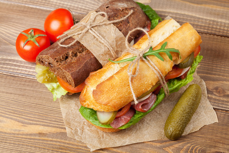 Two sandwiches with salad, ham, cheese and tomatoes on wooden table photo