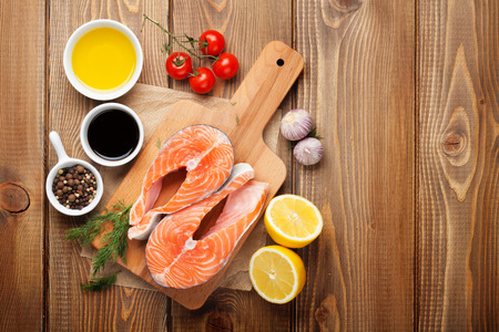 red  fish: Salmon, spices and condiments on wooden table. Top view with copy space Stock Photo