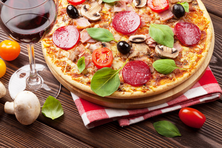 Italian pizza with pepperoni, tomatoes, olives, basil and red wine on wooden table. Top view photo
