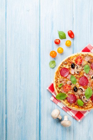 Italian pizza with pepperoni, tomatoes, olives and basil on wooden table. Top view with copy space photo