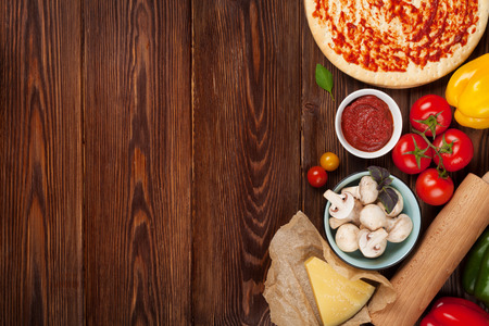 Pizza cooking ingredients. Dough, vegetables and spices. Top view with copy space Archivio Fotografico