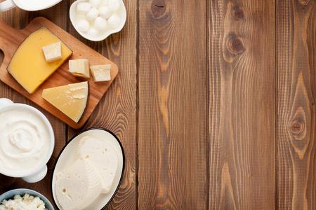 木製テーブルの上の乳製品。サワー クリーム、牛乳、チーズ、ヨーグルト、バター。コピー スペース平面図