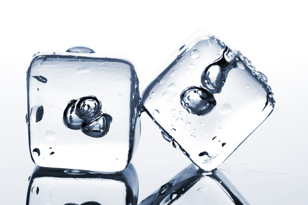 melting ice: Two melting ice cubes with water dew on white background