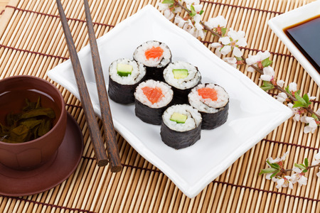 Sushi maki set, green tea and sakura branch over bamboo table photo