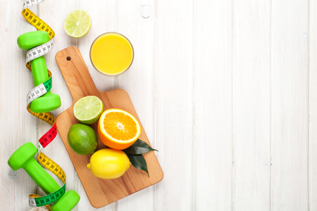 tropical food: Citrus fruits, tape measure and dumbells. Oranges, limes and lemons. Healthy food. Over wood table background with copy space