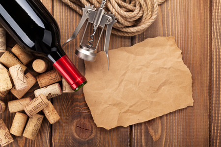 Red wine bottle, corks and corkscrew over wooden table background. Top view with copy space Reklamní fotografie