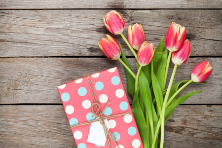 Colorful tulips and gift box on wooden table. Top view with copy space