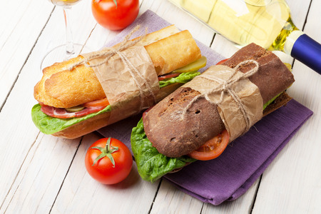 sub sandwich: Two sandwiches and white wine on wooden table