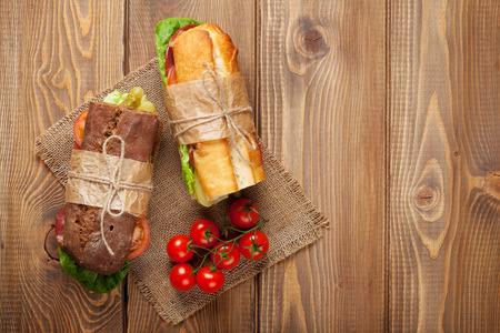 salami: Dos emparedados con ensalada, jamón, queso y tomates en mesa de madera. Vista superior con espacio de copia