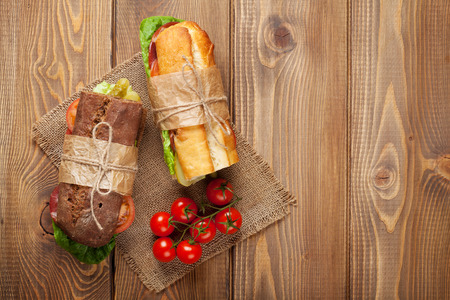 italian salami: Two sandwiches with salad, ham, cheese and tomatoes on wooden table. Top view with copy space