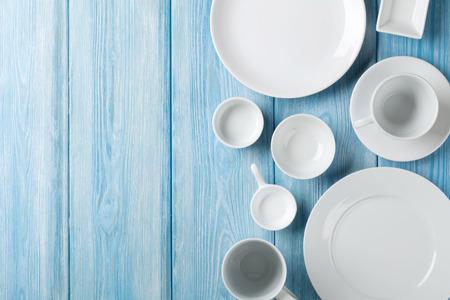 Lege borden en kommen op blauwe houten achtergrond. Bovenaanzicht met een kopie ruimte Stockfoto