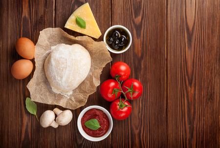 Pizza koken ingrediënten. Deeg, groenten en kruiden. Bovenaanzicht met een kopie ruimte Stockfoto - 39481906