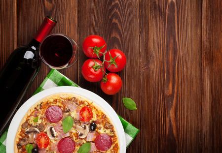 Italian pizza with pepperoni, tomatoes, olives, basil and red wine on wooden table. Top view with copy space photo