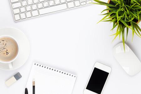 oficina: Mesa escritorio de oficina con el ordenador, los suministros, la flor y la taza de caf�. Vista superior con espacio de copia