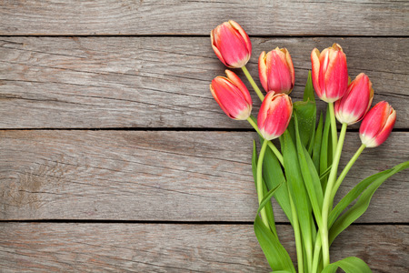 Colorful tulips on wooden table. Top view with copy space photo