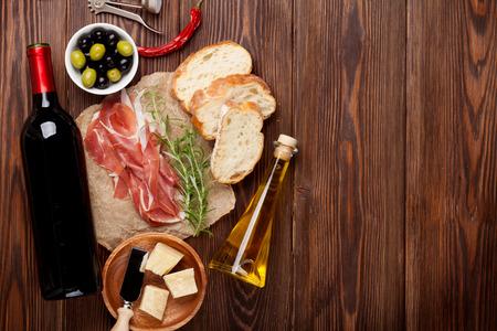jamon y queso: Prosciutto, vino, aceitunas, queso parmesano y aceite de oliva en la mesa de madera. Vista superior con espacio de copia