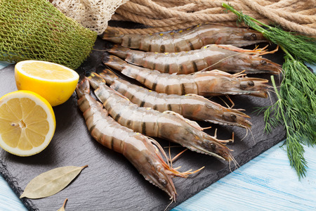 Fresh raw tiger prawns and fishing equipment on wooden table Stock Photo - 39482069