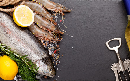 Fresh raw sea food with spices and whtie wine bottle on black stone background. Top view with copy space photo