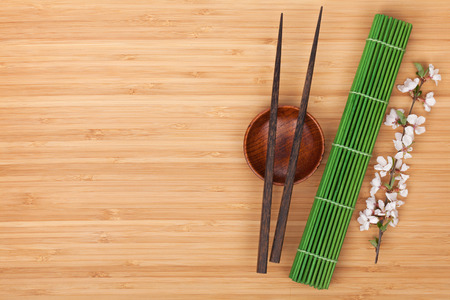 kitchen table top: Chopsticks, sakura branch and bamboo mat on wooden table with copy space