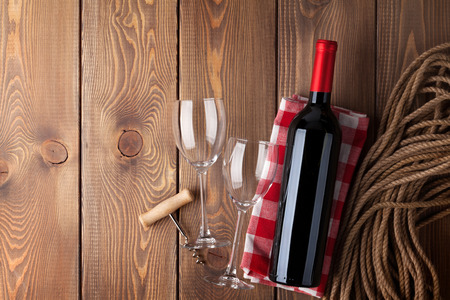 glass table: Red wine bottle, glasses and corkscrew over rustic wooden table background with copy space