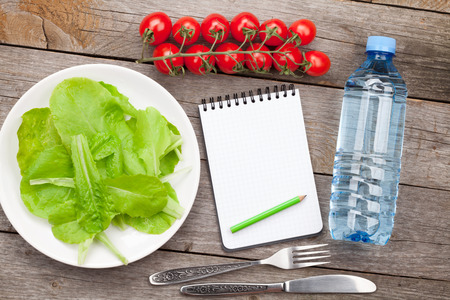 water on leaf: Fresh healthy salad, tomatoes, water bottle and notepad for copy space on wooden table