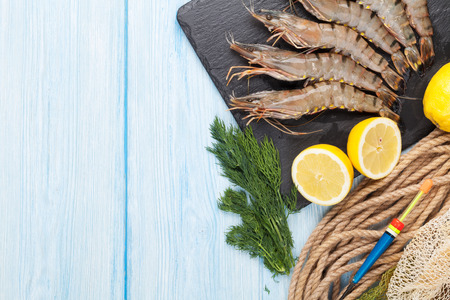 fish net: Fresh raw tiger prawns and fishing equipment on wooden table. Top view with copy space Stock Photo