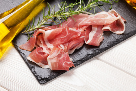 Prosciutto with rosemary and olive oil on wooden table