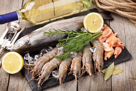 Fresh raw sea food with spices and whtie wine bottle on wooden table background