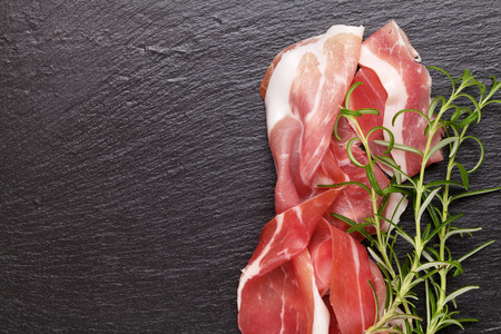cured ham: Prosciutto with rosemary on black stone table