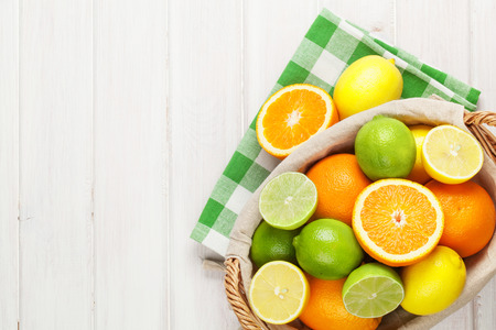 citrus fruit: Citrus fruits in basket. Oranges, limes and lemons. Over white wood table background with copy space